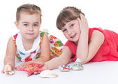 Two little girls are playing and shells and starfish. — Stock Photo