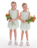 Two charming girls with bouquets of roses. — Stock Photo