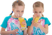Twin sisters love to drink orange juice. — Stock Photo
