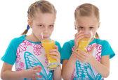 Twin sisters love to drink orange juice. — Stok fotoğraf