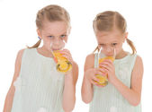 Cute sisters drink from a glass of fresh orange juice. — Стоковое фото