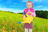 Little girl with a yellow watering — Stock Photo
