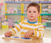 Little boy collects a puzzle — Stock Photo