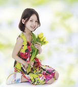 Girl cuddle a bouquet of yellow tulips. — Stock Photo