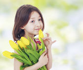 Girl with yellow tulips — Stock Photo
