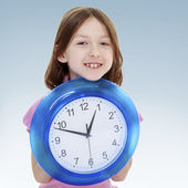 Girl holding a big clock. — Stock Photo