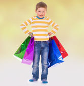Little boy in colorful bags goes to the store. — Photo