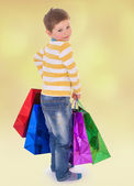 Little boy in colorful bags goes to the store. — Stock Photo