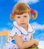 Cute little girl sitting at the table . — Stock Photo