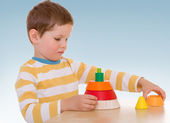 Boy collects pyramid. — Stock Photo