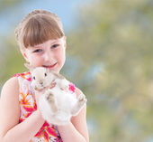 Laughing girl holding a rabbit. — Stock Photo