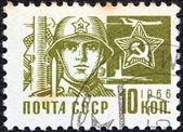 Urss - vers 1966 : un timbre imprimé en Urss de la question « la société et de la technologie » montre un soldat et star emblème, vers 1966. — Photo