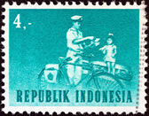 INDONESIA - CIRCA 1964: A stamp printed in Indonesia shows mailman with bicycle, circa 1964. — Foto de Stock
