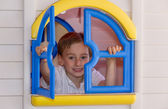 Cute child playing in toy house — Stock Photo