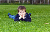 Cute child lying on grass — Stock Photo