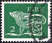 IRELAND - CIRCA 1971: A stamp printed in Ireland shows a dog from an ancient artwork, circa 1971. — Stock Photo