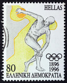 GREECE - CIRCA 1996: A stamp printed in Greece issued for the 100th anniversary of the modern Olympic Games shows an ancient discus thrower athlete, circa 1996. — Stock Photo