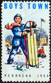 "USA - CIRCA 1964: A stamp printed in USA from the ""Boys Town, Nebraska"" issue shows a boy with sled in snow, circa 1964. — Stock Photo"