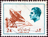 IRAN - CIRCA 1975: A stamp printed in Iran shows Mohammad Reza Pahlavi (the last Shah) and an earth telecommunication station, circa 1975. — Stock Photo