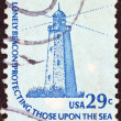 "Stock Photo: US- CIRC1975: stamp printed in USfrom ""Americana"" issue shows Sandy Hook (New Jersey) Lighthouse and inscription ""Lonely Beacon Protecting Those Upon Sea"", circ1975."