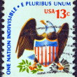 "Stock Photo: US- CIRC1975: stamp printed in USfrom ""Americana"" issue shows eagle and shield and inscription ""One Nation Indivisible-E Pluribus Unum"", circ1975."