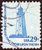 """Usa - circa 1975: een stempel gedrukt in de Verenigde Staten uit de uitgifte van """"americana"""" toont de vuurtoren zandstrand haak (new jersey) en de inscriptie """"eenzame baken bescherming die op de zee"""", circa 1975. — Stockfoto"""