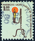 "USA - CIRCA 1975: A stamp printed in USA from the ""Americana"" issue shows the Rush Lamp and Candle Holder and the inscription ""America's Light Fueled by Truth and Reason"", circa 1975. — Photo"