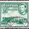 CYPRUS - CIRCA 1938: A stamp printed in Cyprus shows Kyrenia Harbour and King George VI, circa 1938. - Stock Photo