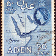 Royalty-Free Stock Photo: ADEN COLONY - CIRCA 1953: A stamp printed in United Kingdom shows map of Arabian peninsula and Queen Elizabeth II, circa 1953.