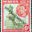 Stock Photo: MALT- CIRC1948: stamp printed in Maltshows statue of Manoel de Vilhenand King George VI (Self-government 1947 overprint), circ1948.