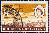 """RHODESIA AND NYASALAND - CIRCA 1960: A stamp printed in Rhodesia from the """"Opening of Kariba Hydroelectric Scheme"""" issue shows 330 kV power lines and Queen Elizabeth II, circa 1960. — Stock Photo"""