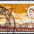RHODESIA AND NYASALAND - CIRCA 1960: A stamp printed in Rhodesia from the &quot;Opening of Kariba Hydroelectric Scheme&quot; issue shows 330 kV power lines and Queen Elizabeth II, circa 1960. - Stock Photo