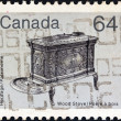 "CANADA - CIRCA 1982: A stamp printed in Canada from the ""Heritage Artifacts"" issue shows a wooden kitchen stove, circa 1982. — Stock Photo"
