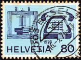 SWITZERLAND - CIRCA 1976: A stamp printed in Switzerland issued for the telephone centenary shows telephones of 1876 and 1976, circa 1976. — Stock Photo