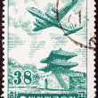 图库照片: SOUTH KORE- CIRC1954: stamp printed in South Koreshows Douglas DC-6 over East Gate, Seoul, circ1954.