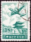 SOUTH KOREA - CIRCA 1954: A stamp printed in South Korea shows Douglas DC-6 over East Gate, Seoul, circa 1954. — Foto de Stock