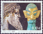 GREECE - CIRCA 2007: A stamp printed in Greece issued for the Cultural Year of Greece in China shows Zeus of Artemision statue and bronze head sculpture with golden mask, Shang dynasty, circa 2007. — Stock Photo