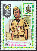 "MANAMA DEPENDENCY - CIRCA 1971: A stamp printed in United Arab Emirates from the ""13th World Jamboree of the Boy Scouts in Japan"" issue shows boy scout from Singapore, circa 1971. — Stock Photo"