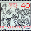 GERMANY - CIRCA 1974: A stamp printed in Germany issued for the 700th death anniversary of St. Thomas Aquinas shows St. Thomas teaching pupils, circa 1974. — Stock Photo