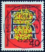 GERMANY - CIRCA 1973: A stamp printed in Germany issued for the 1000th death anniversary of Roswitha von Gandersheim (poetess) shows a motif with letter R, circa 1973. — Stock Photo