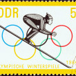 "GERMAN DEMOCRATIC REPUBLIC - CIRCA 1963: A stamp printed in Germany from the ""Winter Olympic Games, Innsbruck, 1964"" issue shows Ski Jumper commencing Run, circa 1963. — Stock Photo #31273563"