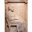 Stock Photo: Greek marble grave stele from Piraeus shows bearded msits on chair holding staff.
