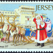 "JERSEY - CIRCA 1997: A stamp printed in United Kingdom from the ""Christmas. Santa Claus at various Jersey landmarks "" issue shows Santa Claus outside Jersey airport, circa 1997. — Stock Photo"