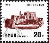 северная корея - около 1995: марку, напечатанную в северной корее от вопроса «машины» показывает бульдозер, около 1995. — Стоковое фото