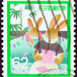 JAPAN - CIRCA 1989: A stamp printed in Japan issued for the letter writing day shows Mother Rabbit reading letter, circa 1989. — Stock Photo