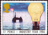 """UNITED KINGDOM - CIRCA 1986: A stamp printed in United Kingdom from the """"Industry Year """" issue shows light bulb and North Sea oil drilling rig (Energy), circa 1986. — Stock Photo"""