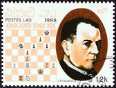 """LAOS - CIRCA 1988: A stamp printed in Laos from the """"Chess Masters """" issue shows Jose Raul Capablanca, circa 1988. — 图库照片"""