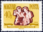 "HUNGARY - CIRCA 1958: A stamp printed in Hungary from the ""Savings Campaign "" issue shows schoolboys with savings stamps, circa 1958. — Stock Photo"