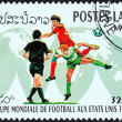 "LAOS - CIRCA 1994: A stamp printed in Laos from the ""World Cup Football Championship, U.S.A."" 4th issue shows soccer players on world map, circa 1994. — Stock Photo"