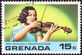 GRENADA - CIRCA 1978: A stamp printed in Grenada issued for the 150th Anniversary of Beethoven Death shows woman violinist, circa 1978. — Stock Photo